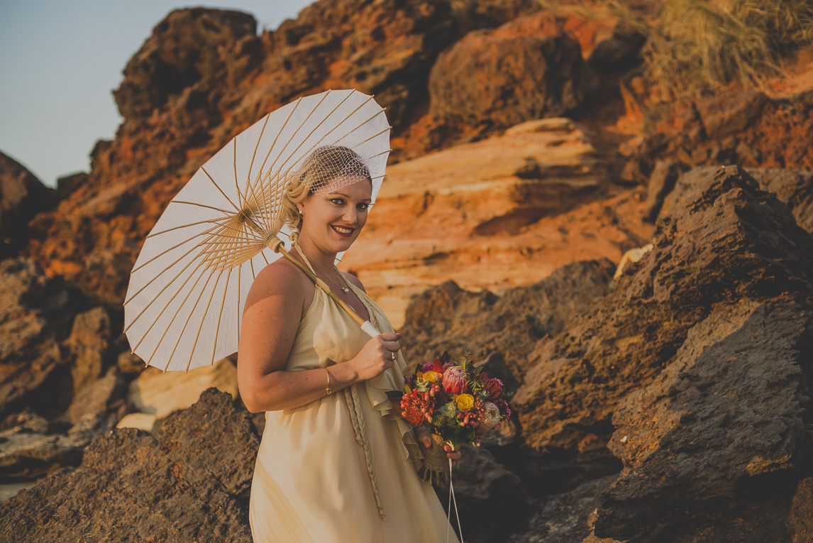 rozimages - wedding photography - bride smiling with umbrella, in front of rocks - Broome, Australia