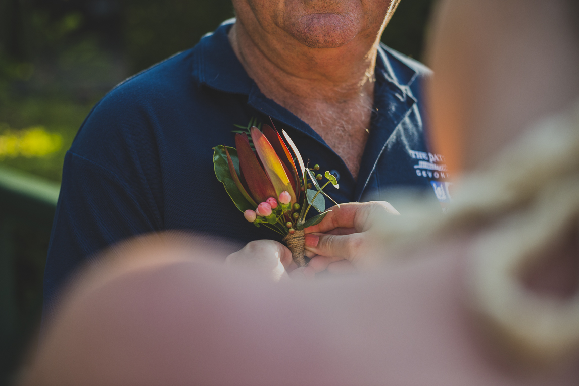 rozimages - wedding photography - close-up on boutonniere being pinned to shirt - Broome, Australia