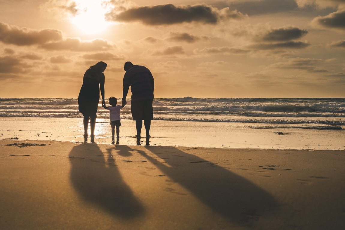 Silhouettes of family on beach photographed by rozimages