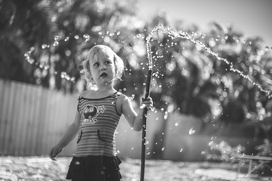 Petite fille jouant avec le tuyau d'arrosage dans le jardin. Photographe de famille en Toulouse
