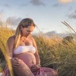 rozimages - portrait photography - maternity pregnancy session - pregnant woman sitting among tall grass at sunset - Perth, Australia