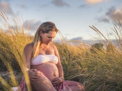 Séance photo grossesse – femme enceinte assise parmis les herbes hautes