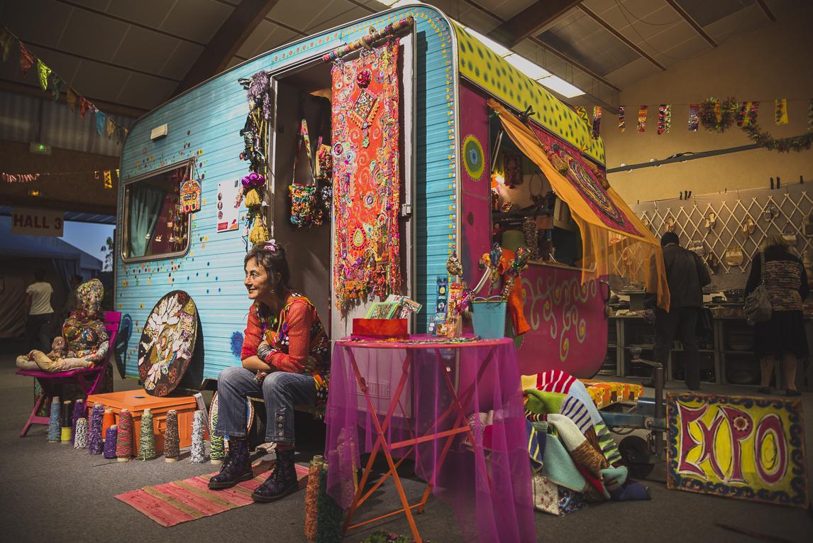 rozimages - photographie évènementielle - Salon des Arts et du Feu 2015 - caravane colorée et artiste assise devant sa porte - Martres-Tolosane, France