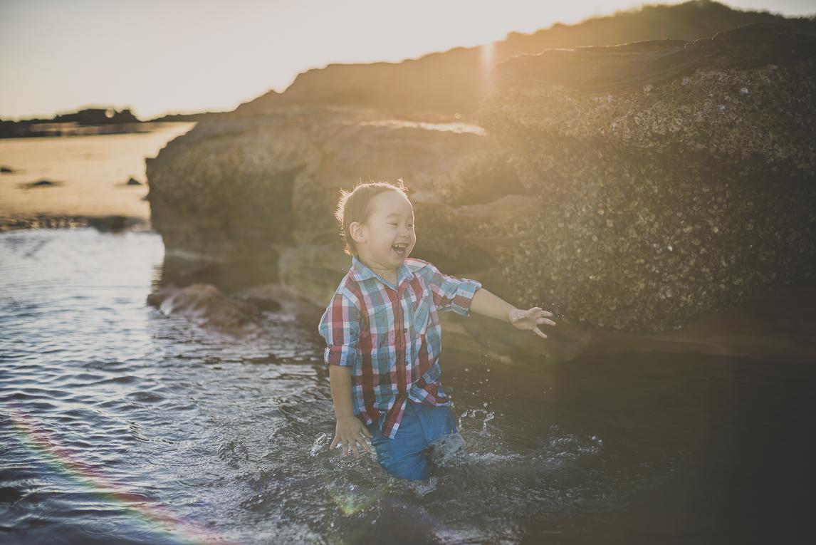 rozimages - photographie de famille - session à la plage - garçon jouant et s'éclaboussant dans l'eau près d'un rocher - Reddell Beach, Broome, Australie