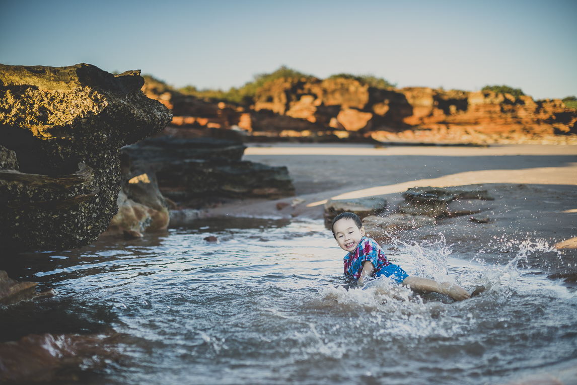 rozimages - family photography - beach session - boy playing and splashing in water near rock - Reddell Beach, Broome, Australia