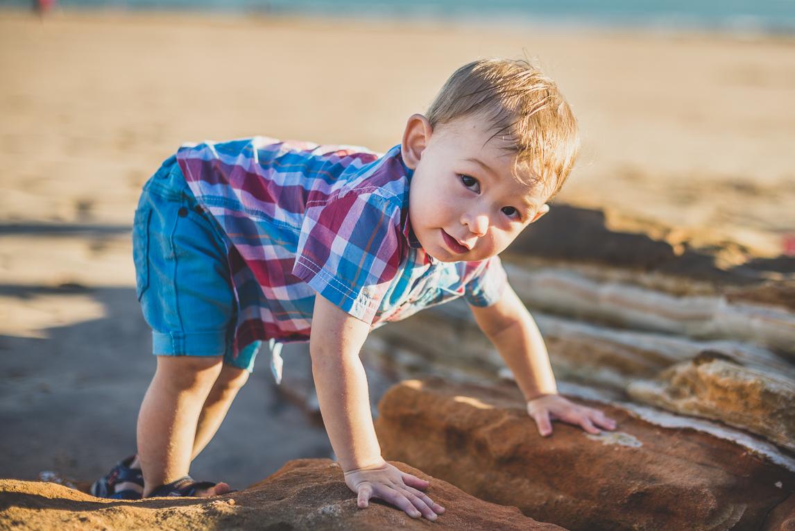 rozimages - photographie de famille - session à la plage - petit garçon grimpant un rocher - Reddell Beach, Broome, Australie