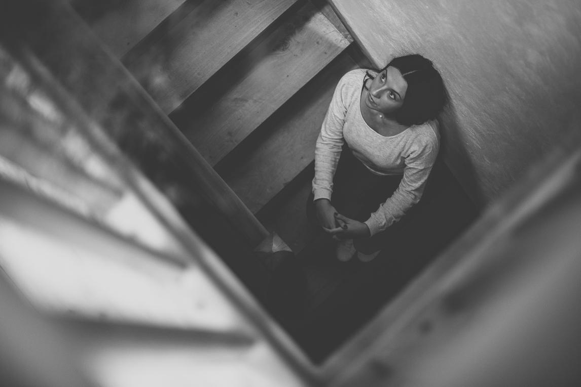 rozimages - photographie lifestyle et portraits - séance individuelle - femme assise dans la cage d'escalier, regardant en l'air, photo prise du dessus - Mondavezan, France