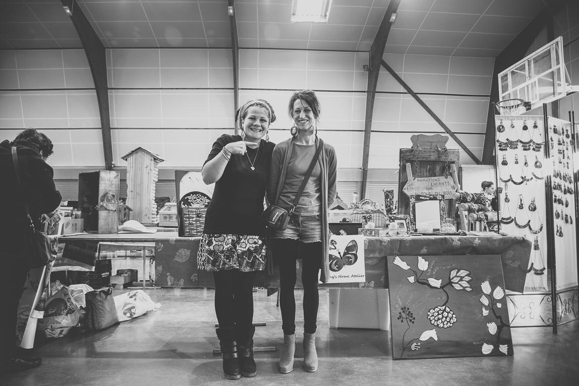 rozimages - photographie d'évènement - évènement communautaire - Marché de Noël 2015 - deux personnes devant stands - Mondavezan, France