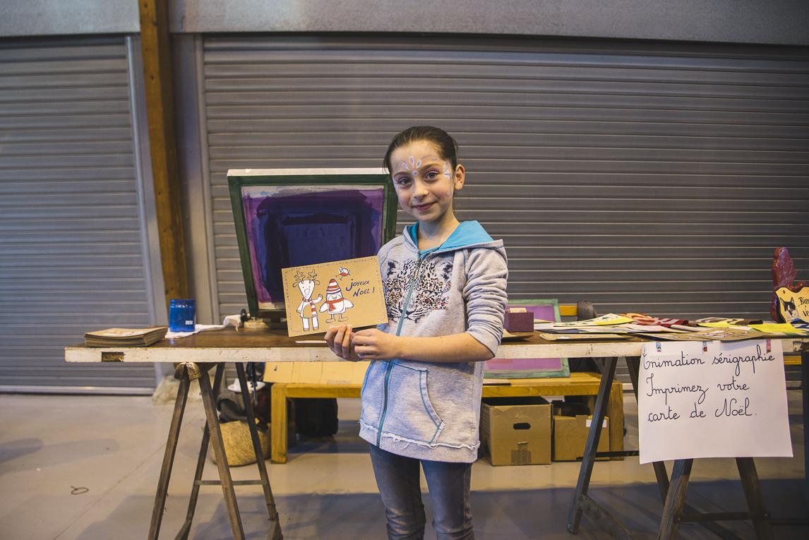 rozimages - photographie d'évènement - évènement communautaire - Marché de Noël 2015 - enfant montrant sa carte de voeux imprimée - Mondavezan, France