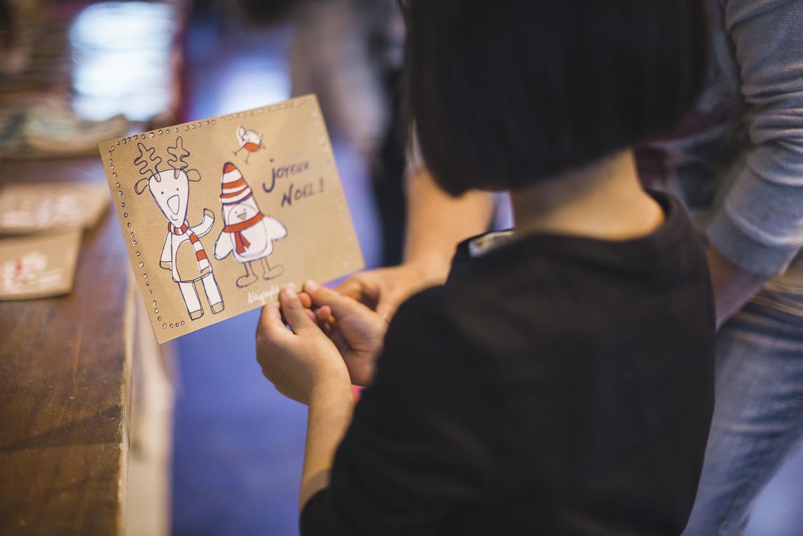 rozimages - photographie d'évènement - évènement communautaire - Marché de Noël 2015 - enfant regardant sa carte de voeux imprimée - Mondavezan, France