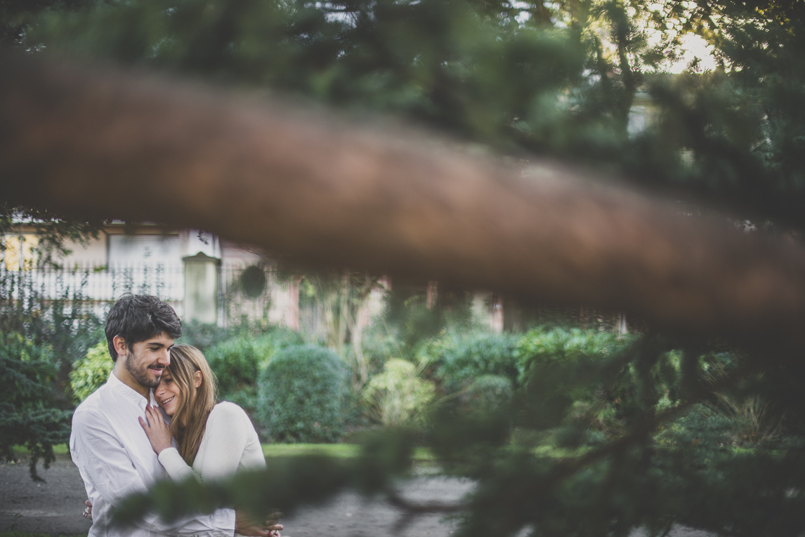 Couple photographer Toulouse - Couple hugging behind tree branches at Jardin des plantes, Toulouse. Photographer: rozimages