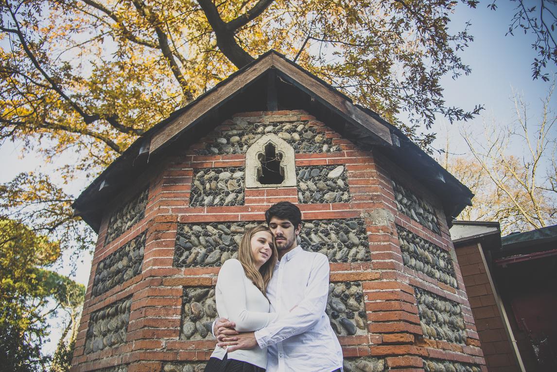 rozimages - photographie de couple - couple se faisant un calin devant une petite maison de pierre - Jardin des plantes, Toulouse, France