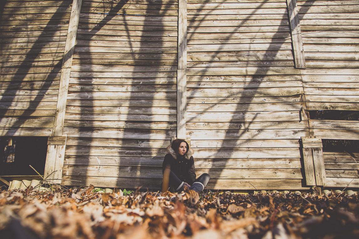 Séance Portrait en Midi-Pyrénées - femme assise contre une cabane en bois - Photographe de Portrait