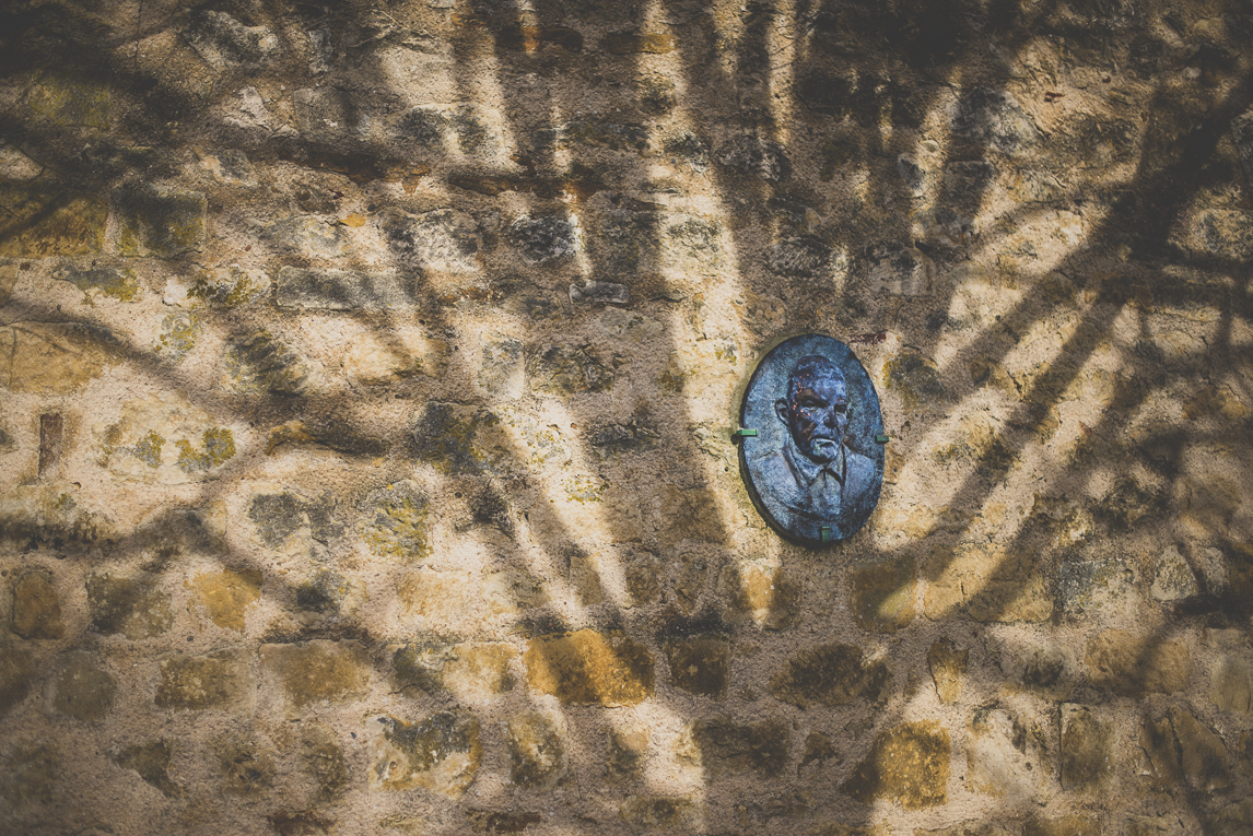 Photo of the French town of Aurignac - relief sculpture on stone wall with tree shadows - Aurignac Photographer