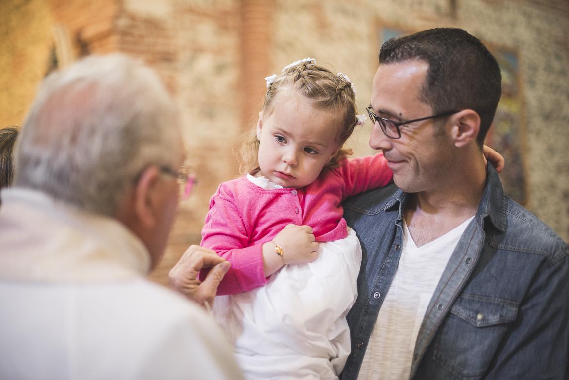 Baptême à Mondavezan - petite fille dans les bras de son papa - Photographe de famille