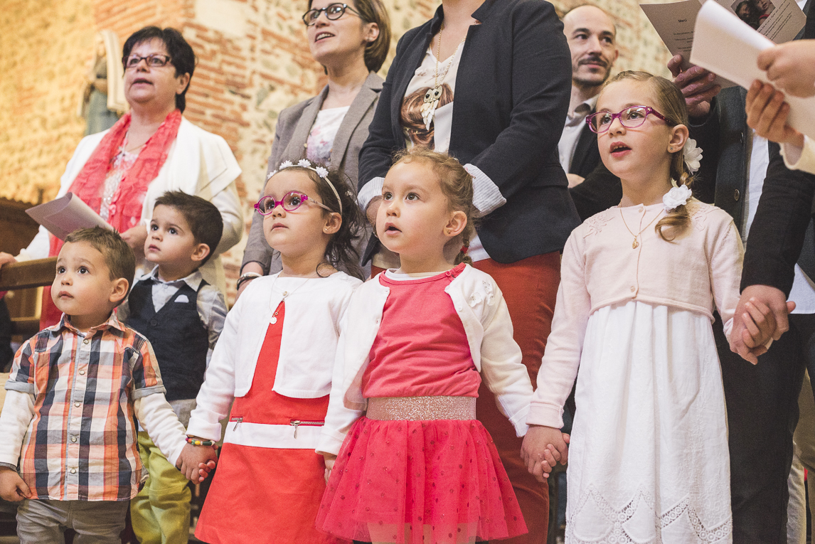 Baptême à Mondavezan - enfants chantant et se tenant la main - Photographe de famille