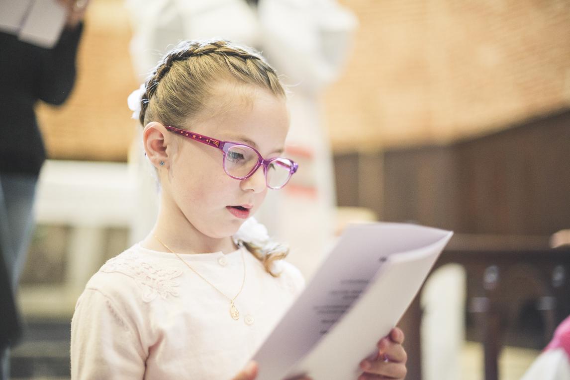 Baptême à Mondavezan - petite fille lisant un livret - Photographe de famille