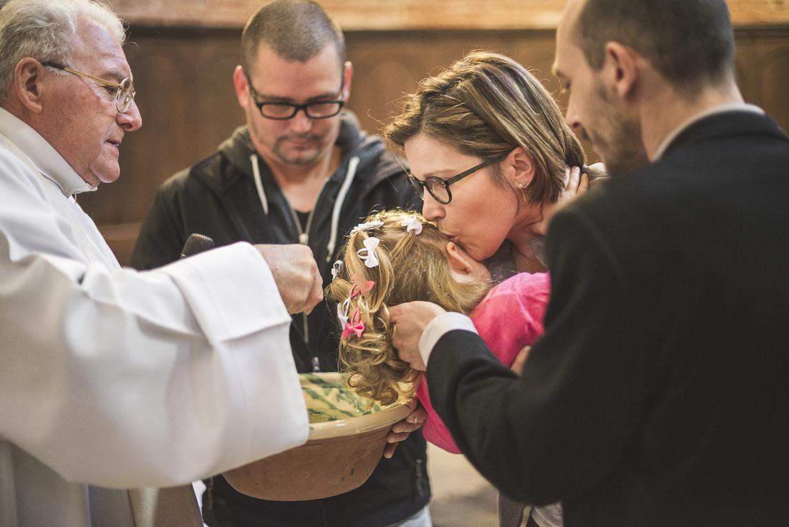 Baptême à Mondavezan - Eau versée sur la tête d'une petite fille - Photographe de famille