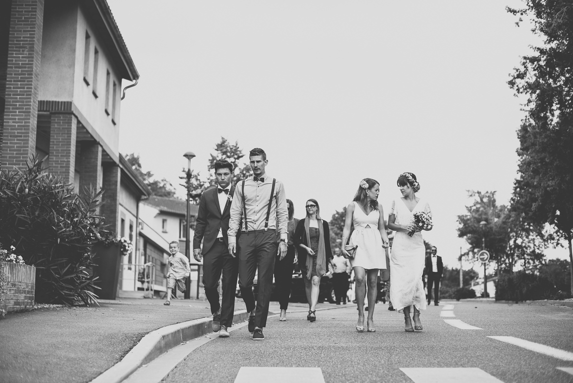 Wedding Photography Toulouse - married couple and guests walking on the road - Wedding Photographer