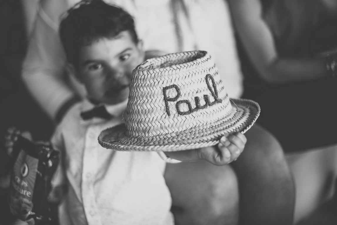 Wedding Photography Toulouse - child shows his personalised straw hat - Wedding Photographer