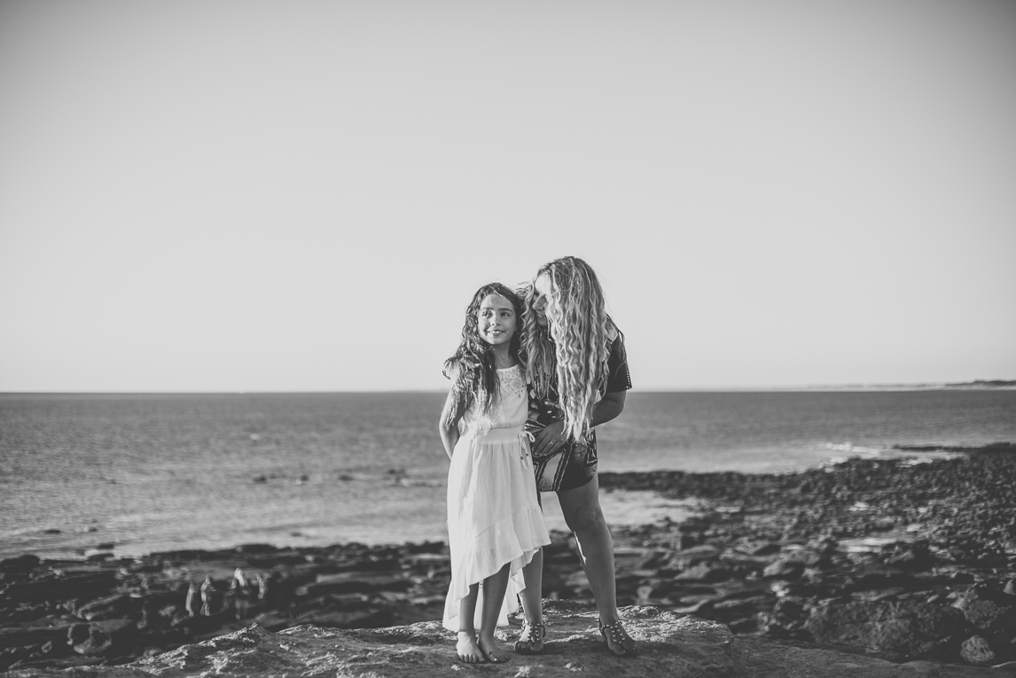Family photo session - child and mum on rocks in front of the sea - Family Photographer