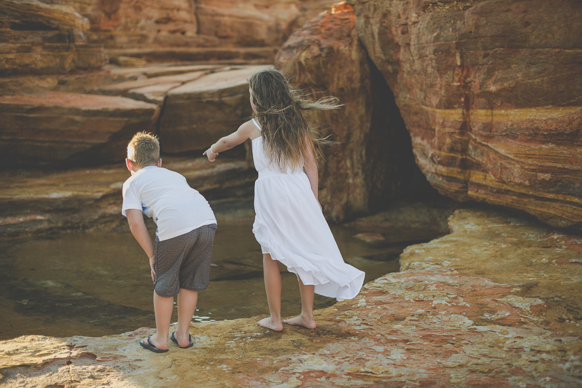 Family photo session - two children look into a pond among rocks - Family Photographer