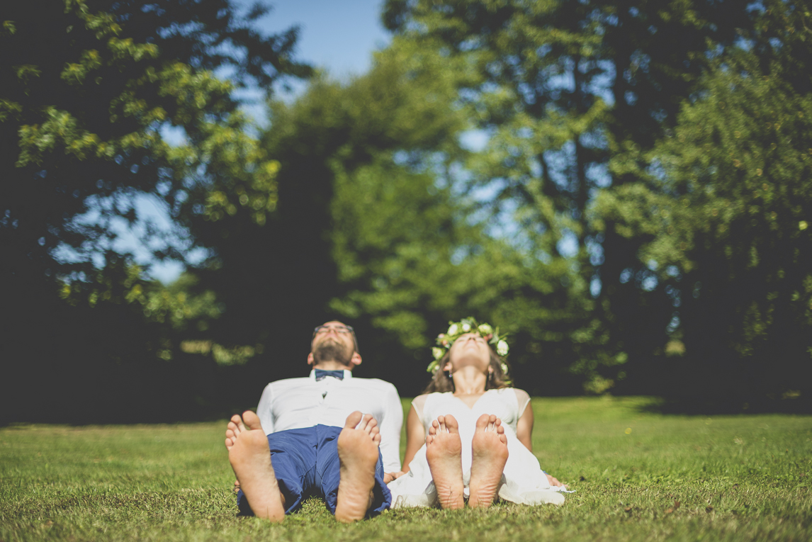 Wedding Photography Brittany - bride and groom lying on the grass - Wedding Photographer