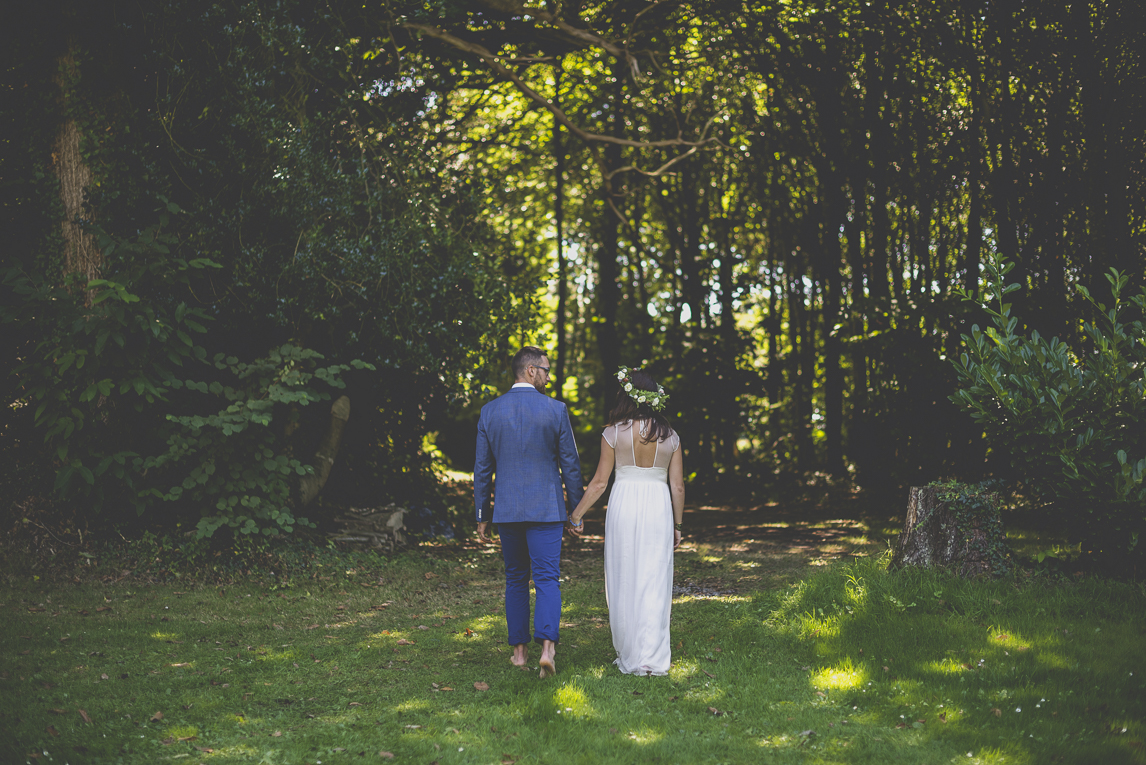 Wedding Photography Brittany - bride and groom from behind walking towards the forest - Wedding Photographer