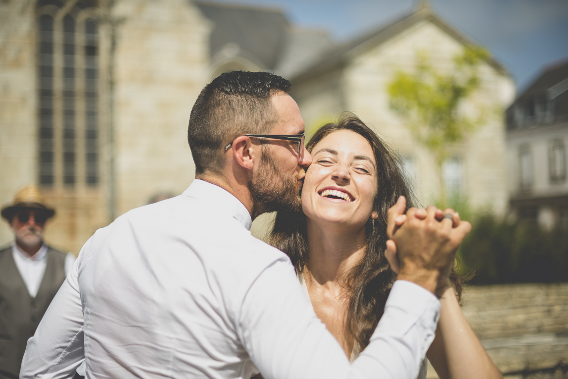 Wedding Photography Brittany - bride and groom kissing in front of town hall - Wedding Photographer