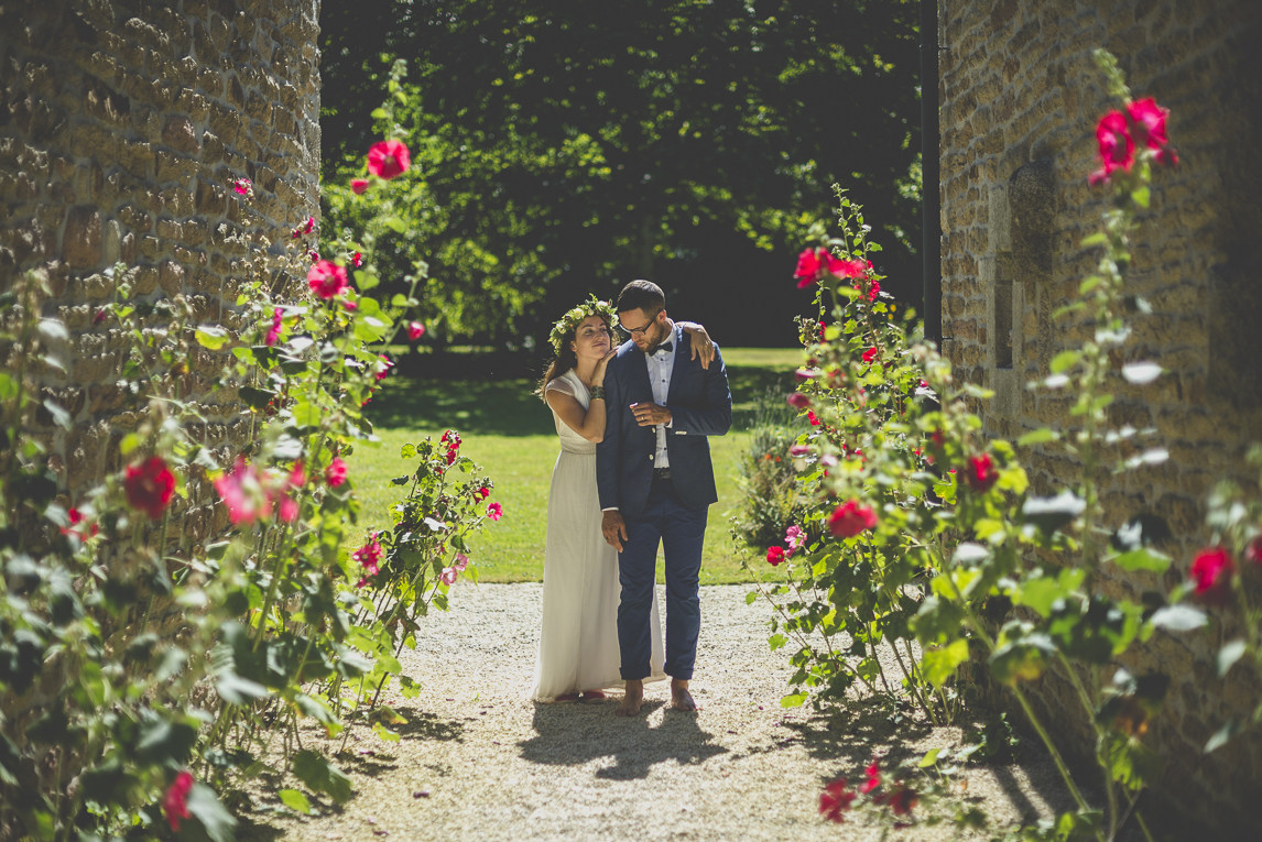 Wedding Photography Brittany - bride and groom among hollyhock flowers - Wedding Photographer