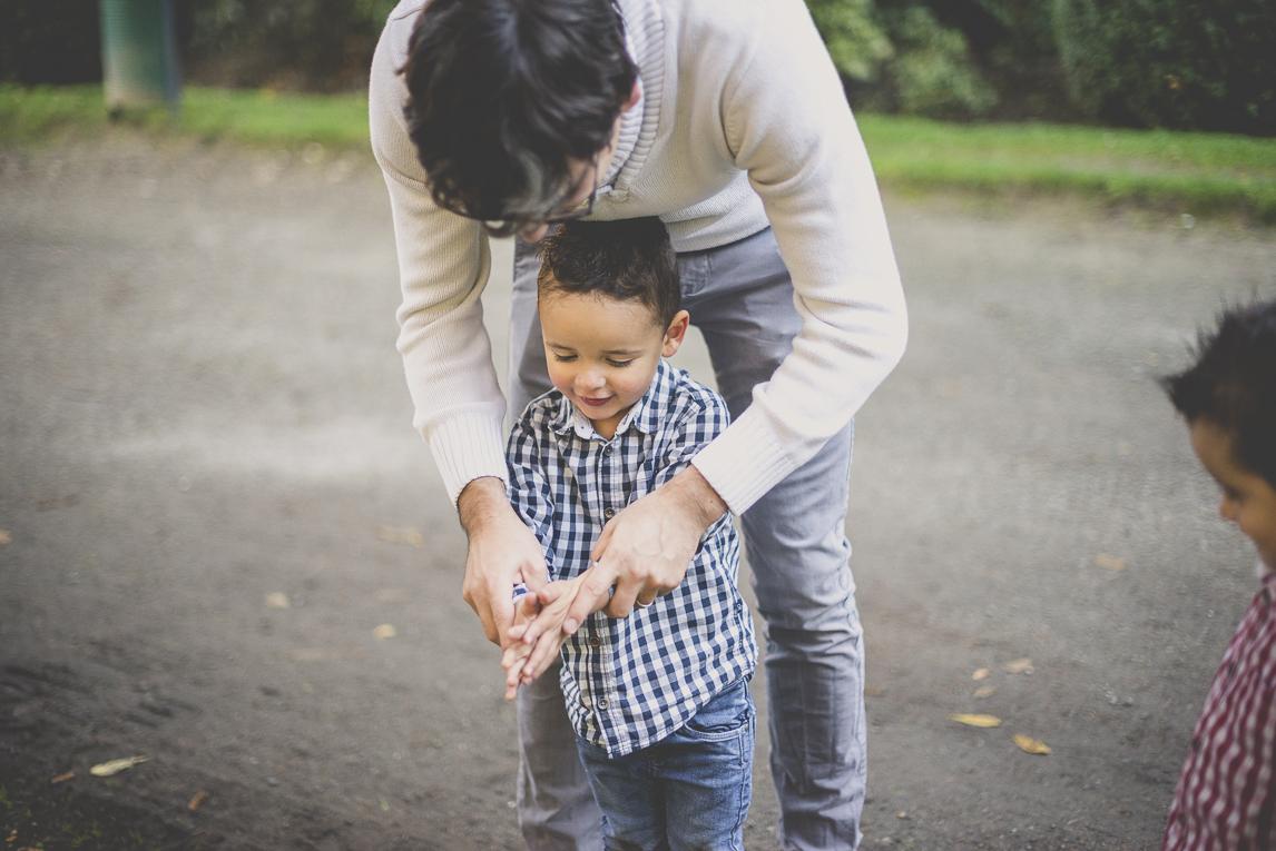 Séance photo famille - papa aide son petit garçon à se frotter les mains - Photographe famille