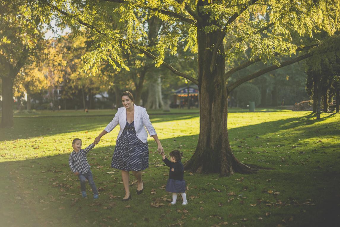 Séance photo famille - mère et ses deux enfants marchent en se donnant la main dans un parc - Photographe famille