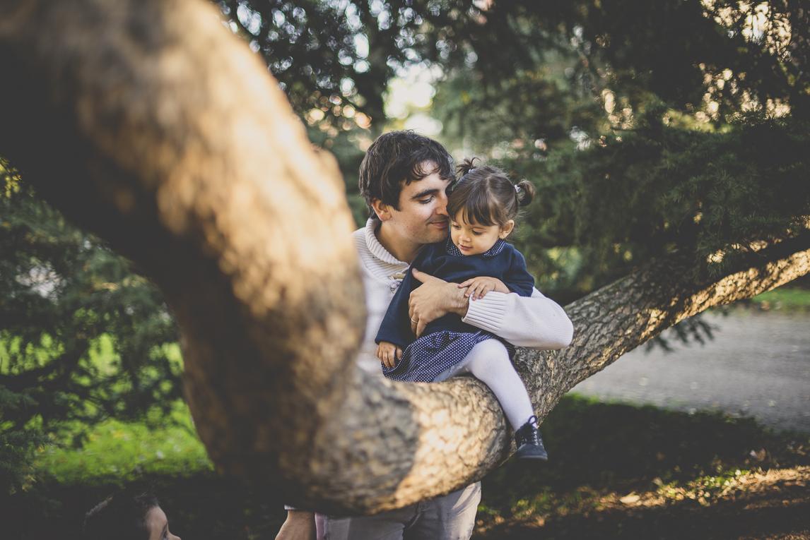 Séance photo famille - papa tient sa petite fille assise sur une branche d'arbre - Photographe famille