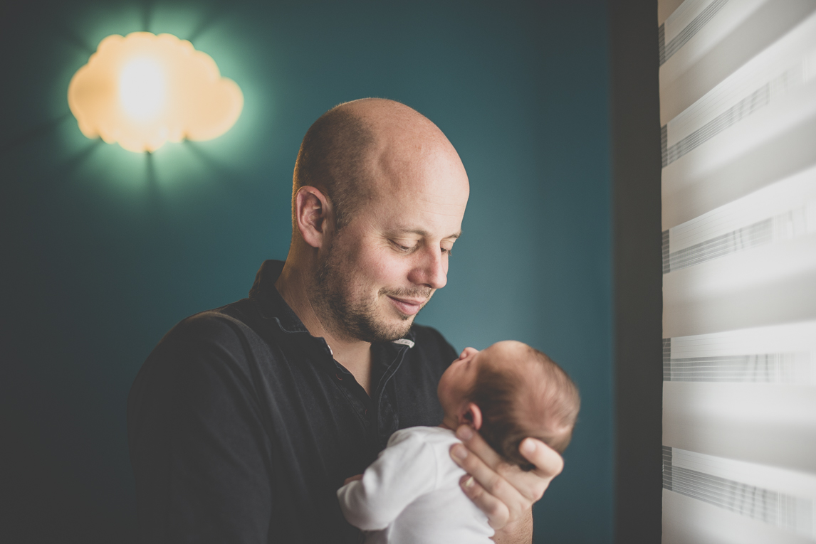 Newborn photo-shoot - dad holds his baby in his arms - Newborn Photographer