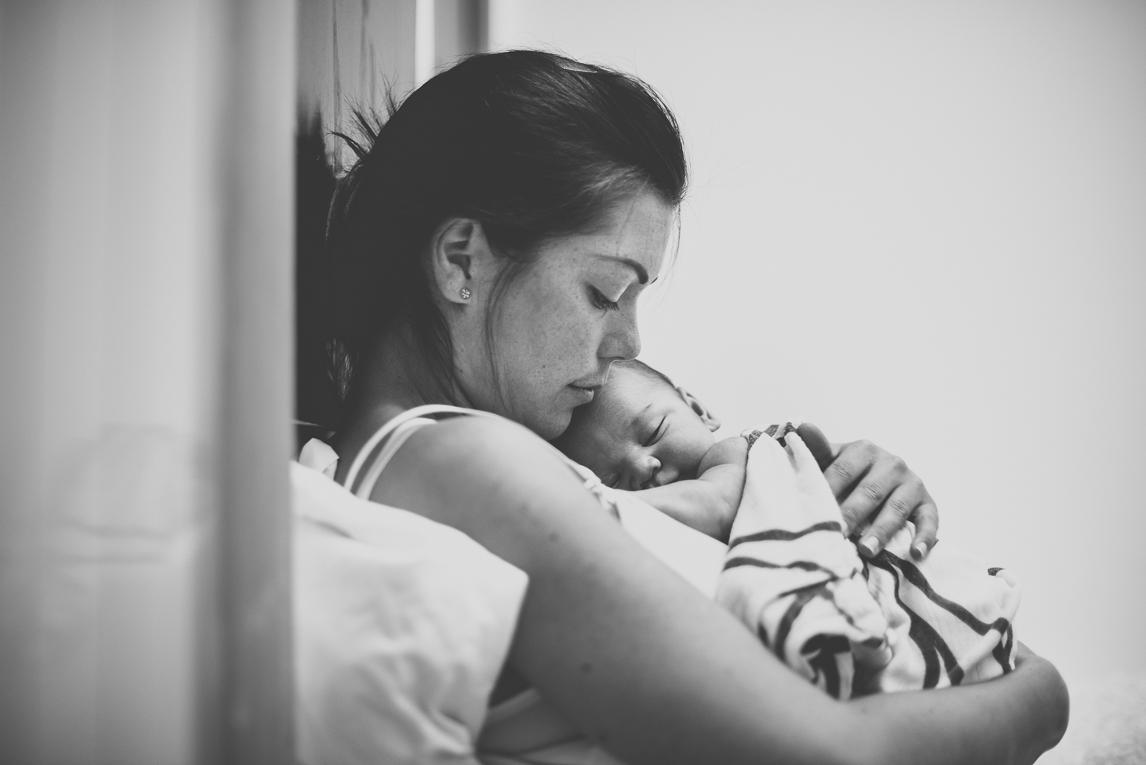 Séance photo naissance à domicile Occitanie - maman tient son nouveau-né dans ses bras - Photographe naissance