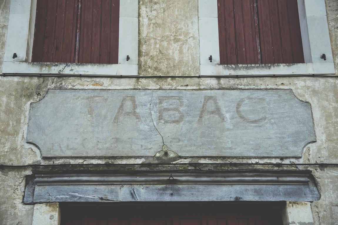 Reportage village Alan - ancien panneau tabac - Photographe voyage