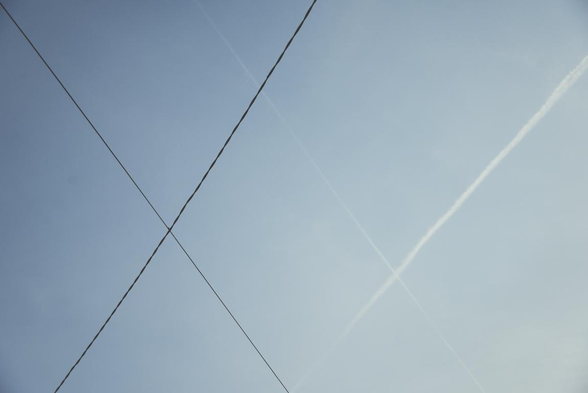 Reportage village Alan - cables électriques et traces d'avion dans le ciel - Photographe voyage