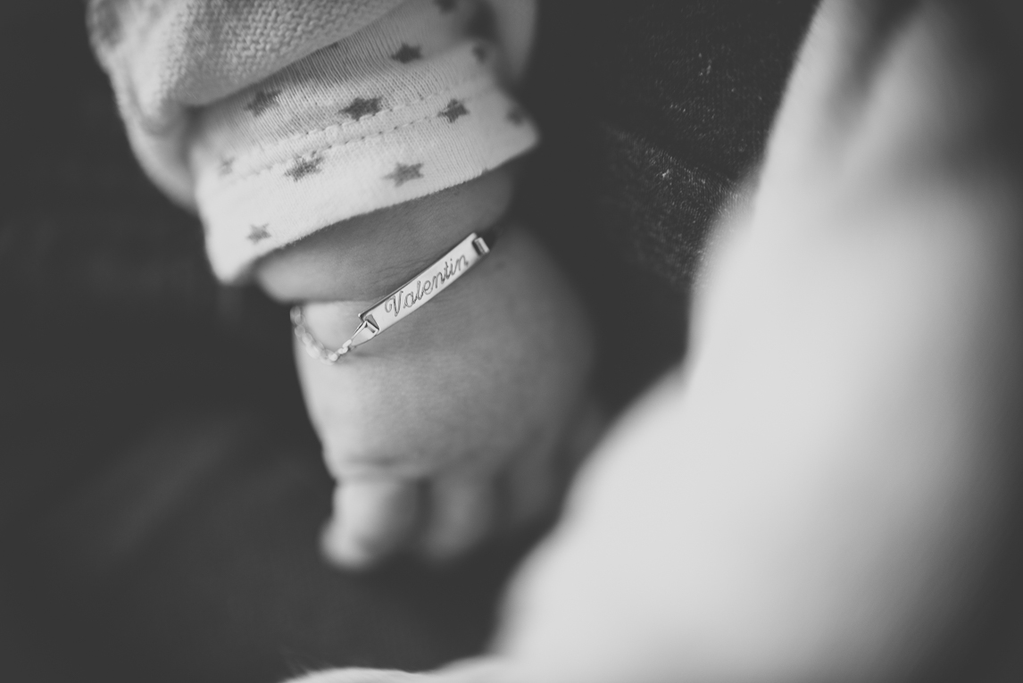 Baby photo session at home - close up on baby's hand and chain bracelet with first name - Baby Photographer