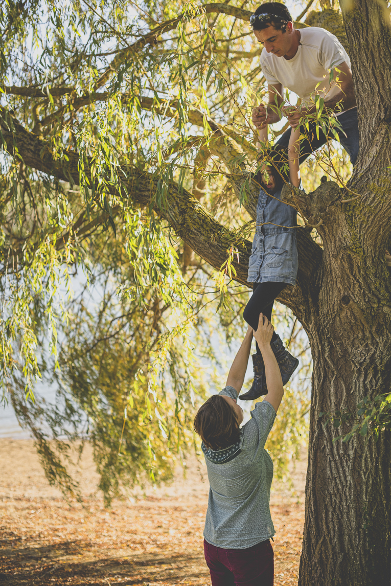 Family photo session Ariège - parents help little girl to come down a tree - Family Photographer