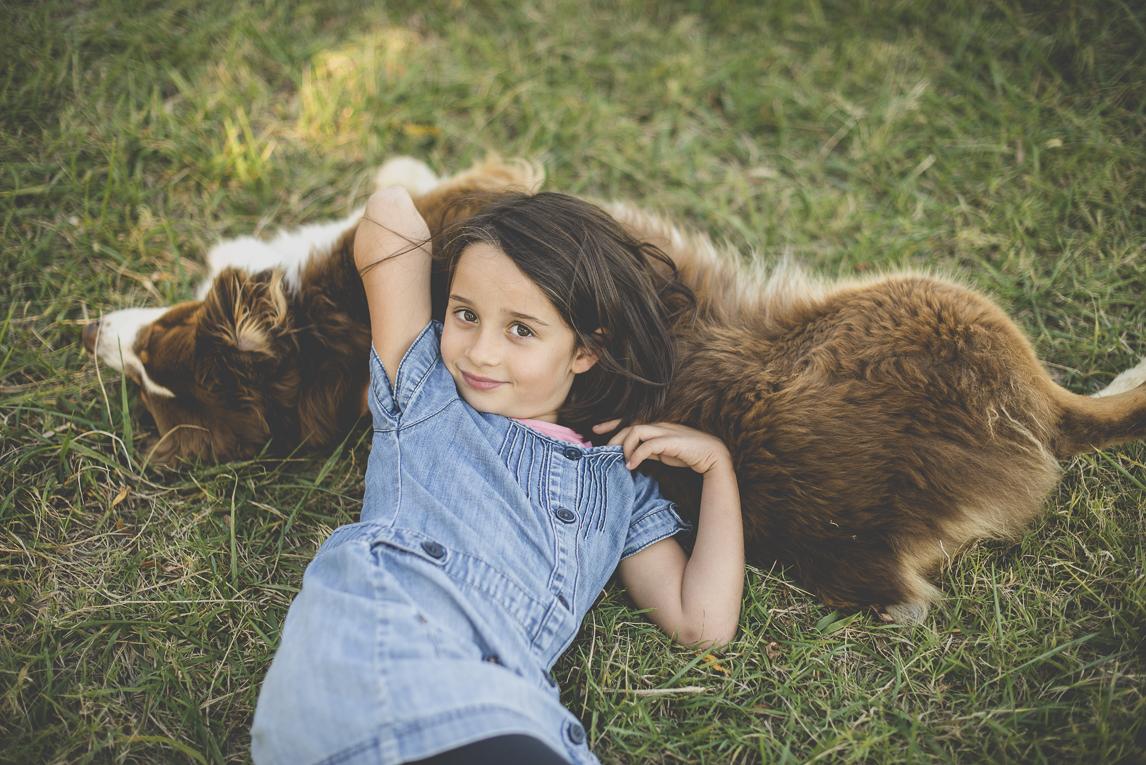 Séance photo en famille Ariège - petite fille allongée avec son chien - Photographe famille