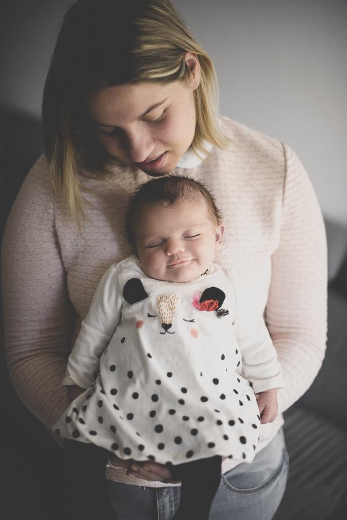 Séance nouveau-né à domicile Saint-Gaudens - bébé endormi et souriant dans bras de maman - Photographe nouveau-né