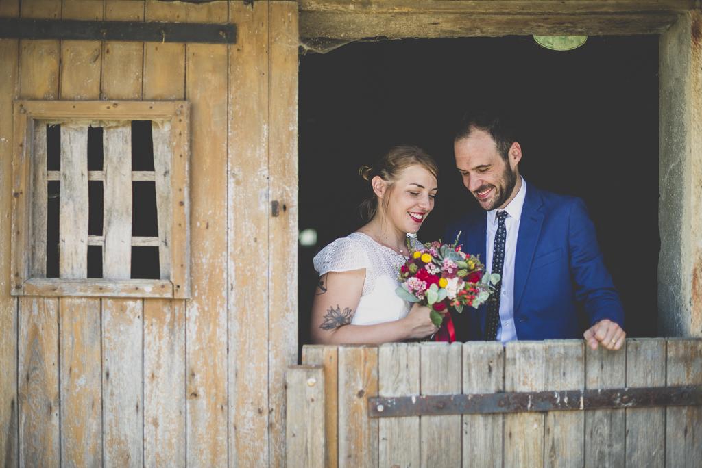 Reportage mariage Haute-Garonne - mariés derrière porte d'étable - Photographe mariage