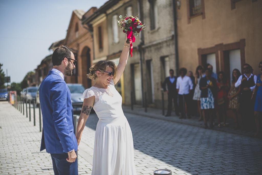 Reportage mariage Haute-Garonne - mariée lève son bouquet devant invités - Photographe mariage