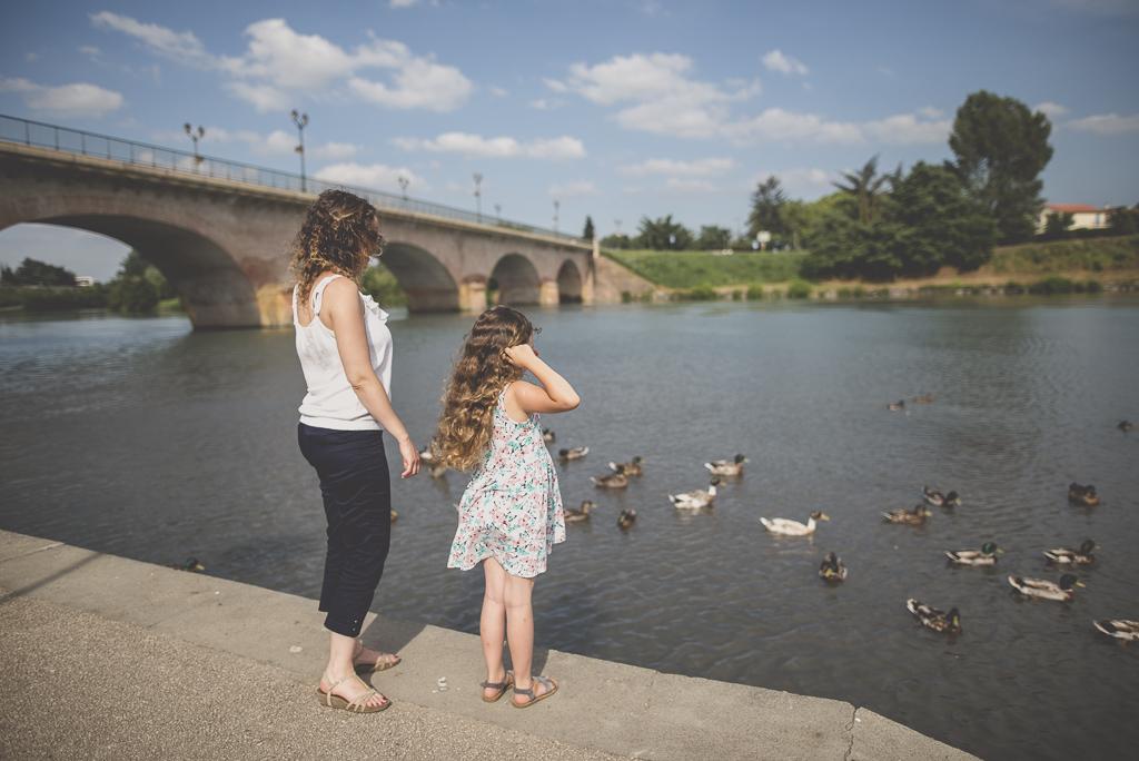 Séance famille Haute-Garonne - mère et fille regardent les canards sur la rivière - Photographe famille Toulouse