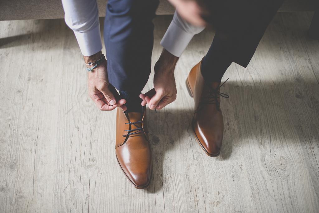 Reportage mariage Auch - Préparatifs du marié - marié met ses chaussures - Photographe mariage Gers