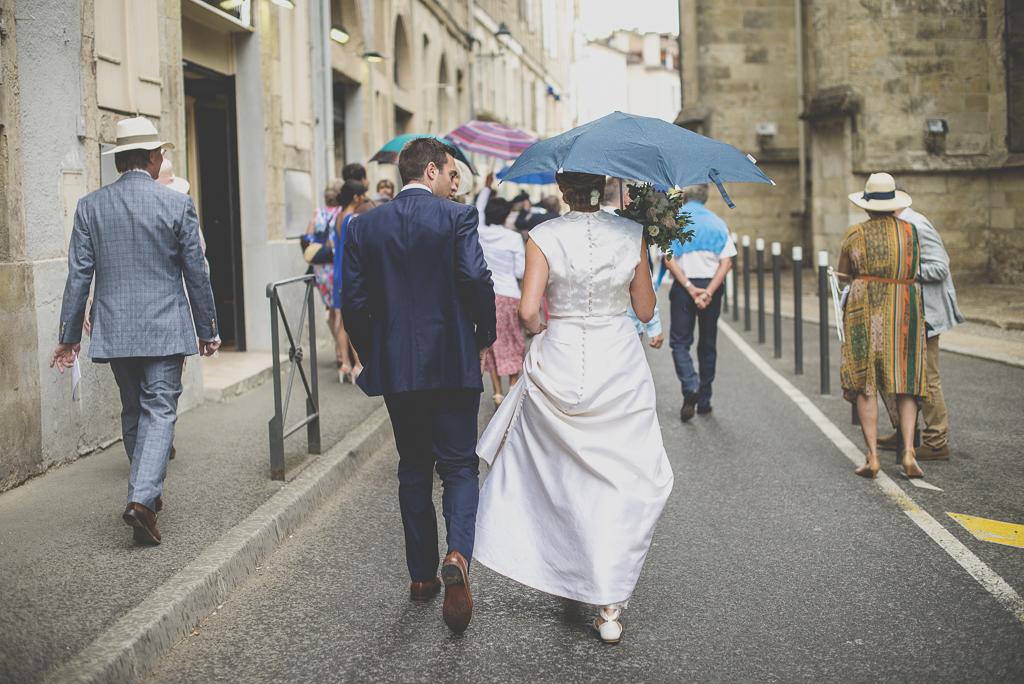 Reportage mariage Auch - mariés marchent avec parapluie - Photographe mariage Gers