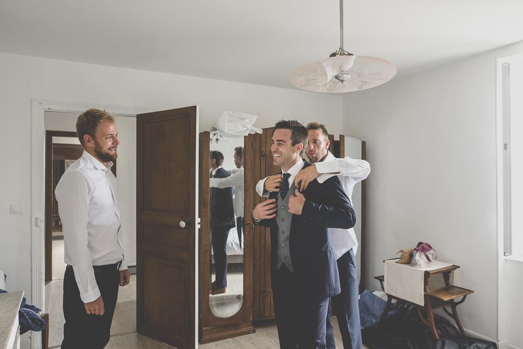 Reportage mariage Auch - Préparatifs du marié - marié met sa veste - Photographe mariage Gers