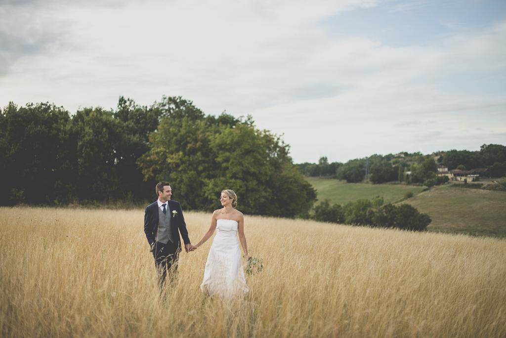 Reportage mariage Auch - Mariés marchent dans champ de blé - Photographe mariage Gers
