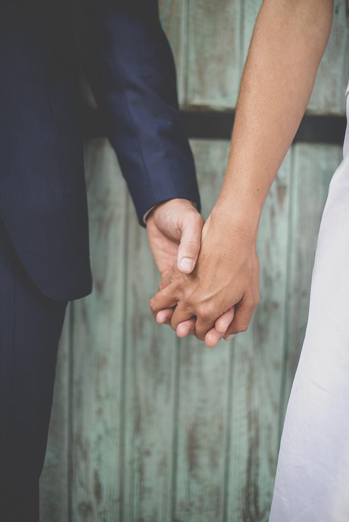 Reportage mariage Auch - mains des mariés devant porte bleue - Photographe mariage Gers