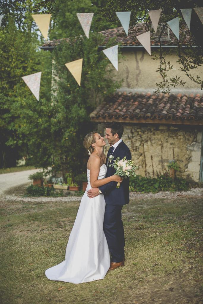 Reportage mariage Auch - mariés enlacés sous fanions - Photographe mariage Gers